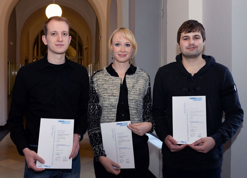 Three people with certificates in their hands